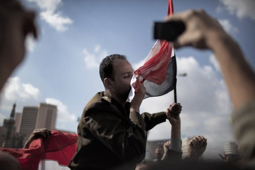 An-Egyptian-army-captain-embraces-a-national-flag-while-being-worn-by-protesters-on-Tahrir-Square-January-31-2011